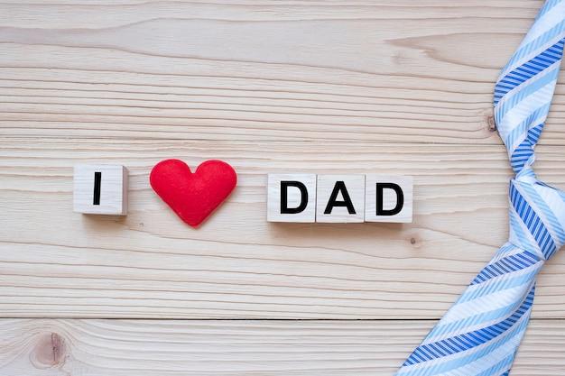 Texte i love dad avec forme de coeur rouge sur bois