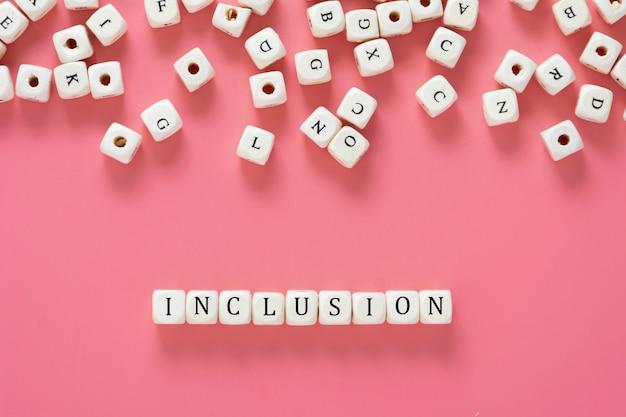 Texte d'inclusion fabriqué à partir de cubes en bois sur une table rose. concept social inclusif. mise à plat.