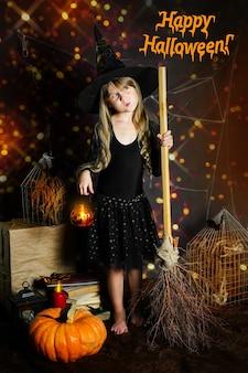 Le texte d'inscription joyeux halloween sur la photo une fille d'âge préscolaire dans un chapeau de sorcière avec un fl de citrouille...