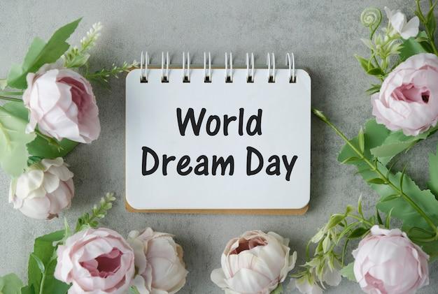 Texte de la journée mondiale du rêve sur le bloc-notes avec des fleurs.