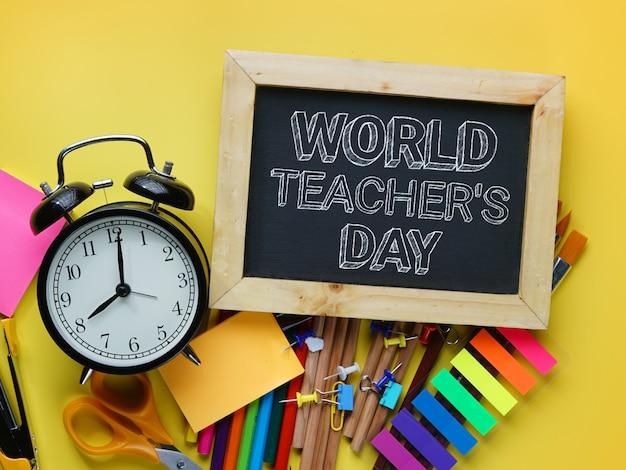 Texte de la journée mondiale des enseignants. réveil, tableau noir et fournitures scolaires sur fond jaune