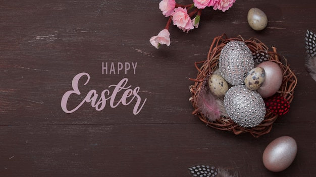 Texte de joyeuses pâques à plat pondre le nid et les œufs sur bakcground brun avec des fleurs de fleurs roses