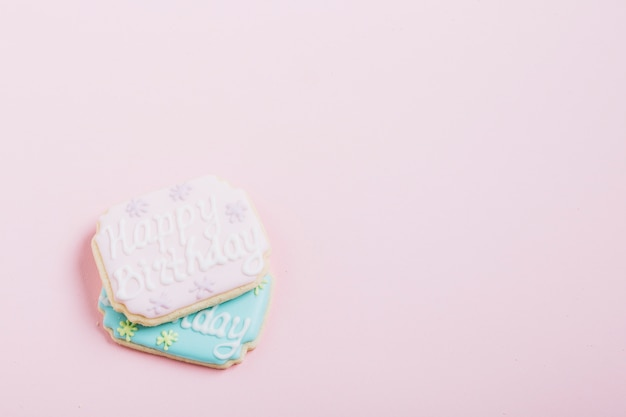 Texte de joyeux anniversaire sur des biscuits frais sur fond rose