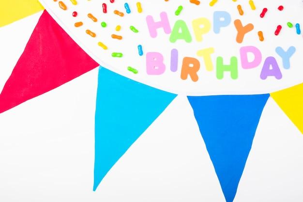 Texte de joyeux anniversaire décoré de bonbons et de banderoles sur fond blanc