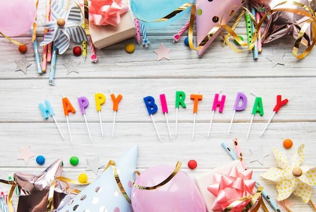 Texte joyeux anniversaire par lettres de bougie avec des accessoires d'anniversaire, des bougies et des confettis sur fond de bois blanc