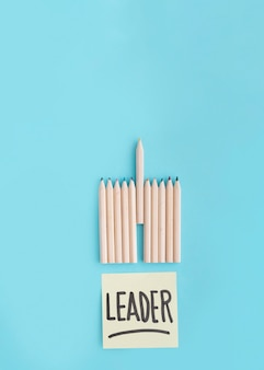 Texte de leader sur une note adhésive avec rangée de crayon de couleur sur fond bleu