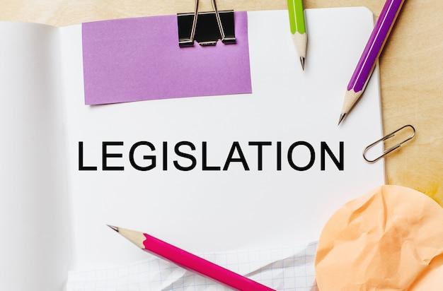 Texte de la législation sur un espace de note blanche avec des crayons, des autocollants et des trombones