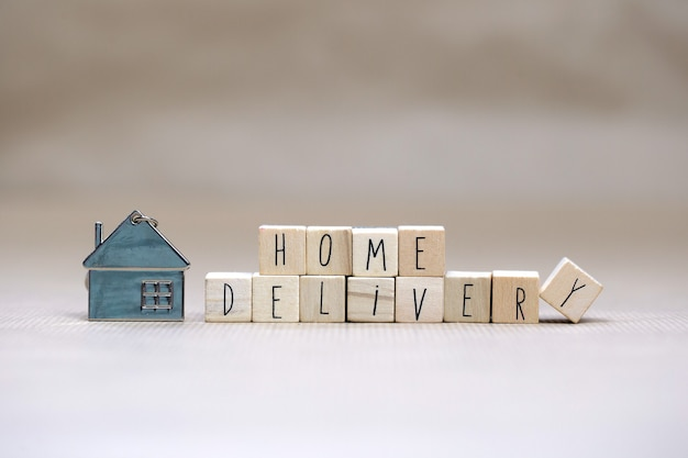 Texte de livraison à domicile avec des cubes en bois et petite maison miniature sur fond flou, business, rester à la maison pour covid-19, nous livrons l'espace de copie d'arrière-plan concept