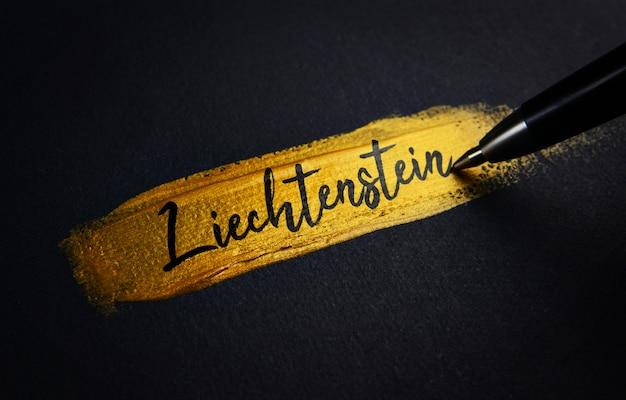 Texte manuscrit du liechtenstein sur le coup de pinceau de peinture dorée