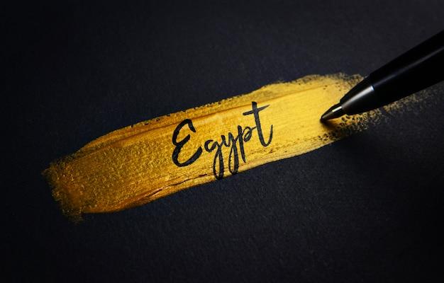 Texte manuscrit d'égypte sur le coup de pinceau de peinture dorée