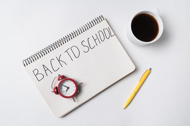 Texte manuscrit retour à l'école bloc-notes sur fond blanc. cahier réveil vintage, stylo et tasse de café. vue de dessus