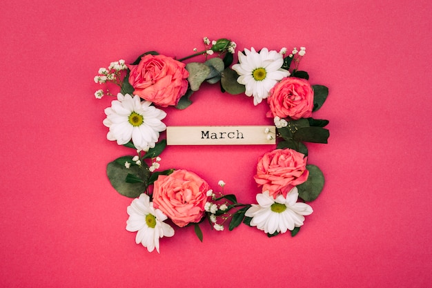Texte de mars à l'intérieur des fleurs blanches et des feuilles décorées sur fond rouge