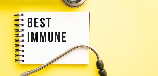 Texte meilleur immunitaire sur ordinateur portable avec stéthoscope sur fond jaune. concept médical.