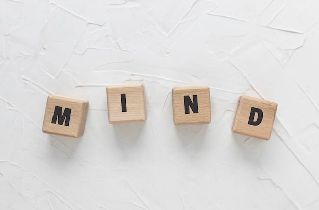 Texte mind fait de cubes de bois sur fond de mastic texturé blanc. blocs de bois carrés. vue de dessus, mise à plat.