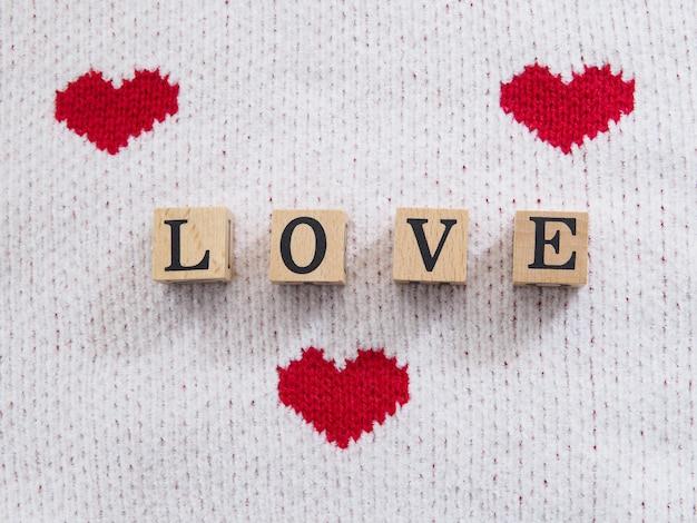 Texte de mot d'amour sur bloc de bois sur tissu blanc avec forme de coeur rouge