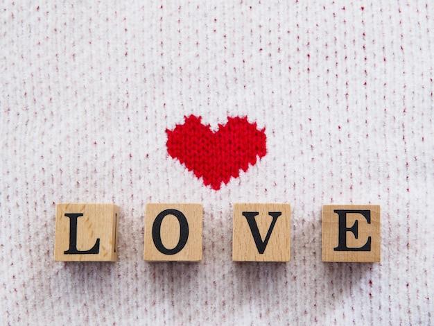 Texte de mot d'amour sur bloc en bois sur tissu blanc avec motif en forme de coeur rouge pour la saint-valentin ou fond de mariage. vue de dessus.