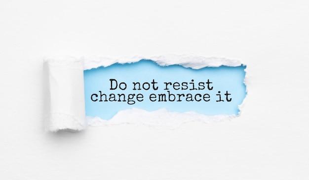 Le texte ne résistez pas au changement embrassez-le apparaissant derrière du papier jaune déchiré