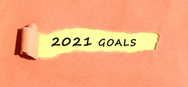 Le texte objectif apparaissant sur papier jaune derrière du papier couleur déchiré vue de dessus