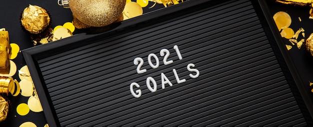 Texte des objectifs 2021 sur tableau à lettres dans un cadre en or décor de fête de noël sur fond noir. fermer.