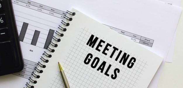 Texte objectifs de réalisation sur la page d'un bloc-notes se trouvant sur les tableaux financiers sur le bureau. près de la calculatrice. concept d'entreprise.