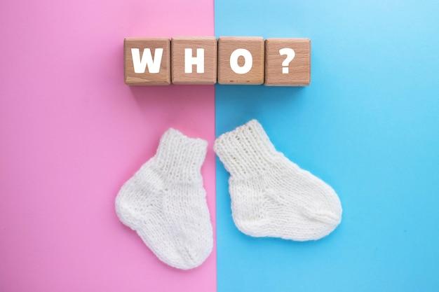 Texte de l'oms sur des cubes de bois et paire de chaussettes tricotées mignonnes sur rose-bleu