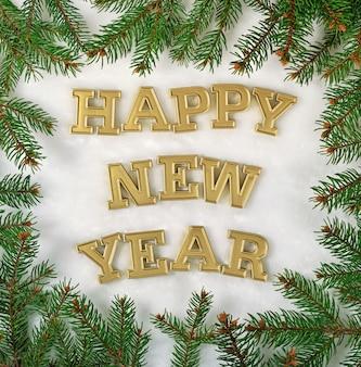 Texte d'or de bonne année et branche d'épinette sur un fond blanc