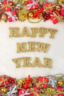 Texte d'or de bonne année et décorations de noël sur un fond blanc