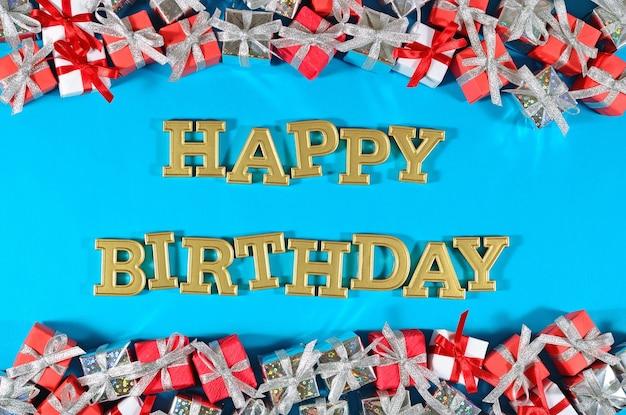 Texte d'or de joyeux anniversaire et cadeaux argentés et rouges sur un bleu