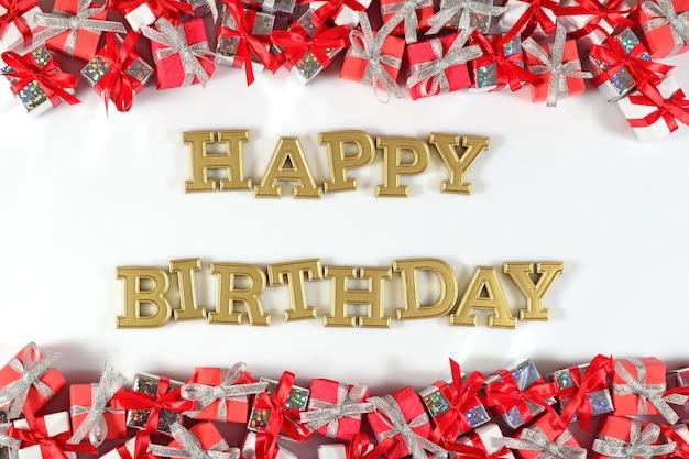 Texte d'or de joyeux anniversaire et cadeaux argentés et rouges sur un fond blanc