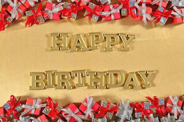 Texte d'or de joyeux anniversaire et cadeaux argentés et rouges sur un fond d'or