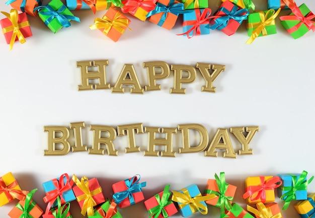 Texte d'or de joyeux anniversaire et cadeaux colorés sur un fond blanc