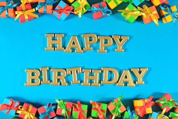 Texte d'or de joyeux anniversaire et cadeaux colorés sur un fond bleu