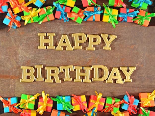 Texte d'or de joyeux anniversaire et cadeaux colorés sur un fond en bois