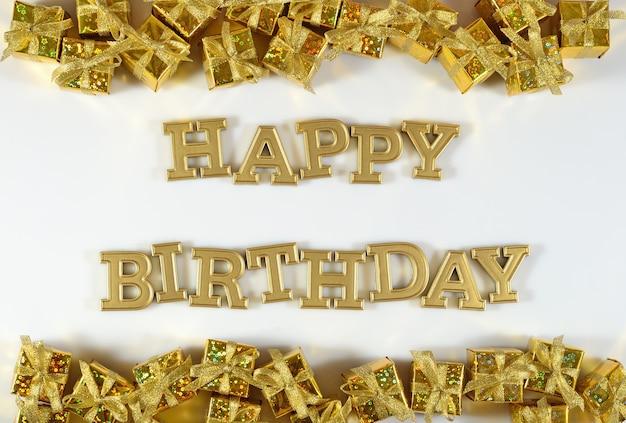 Texte d'or de joyeux anniversaire et cadeaux d'or sur un fond blanc