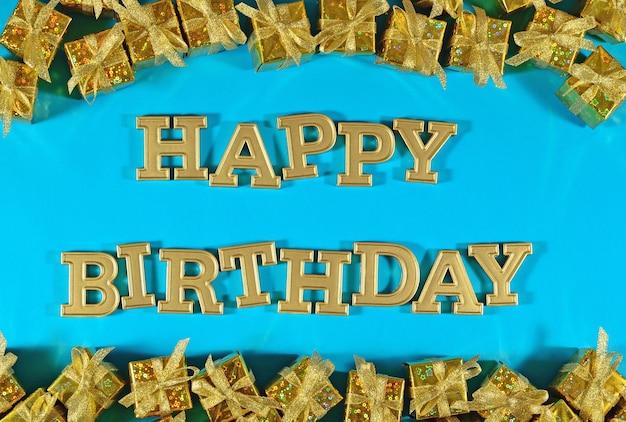 Texte d'or de joyeux anniversaire et cadeaux d'or sur un fond bleu