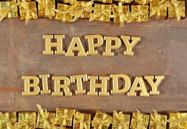 Texte d'or de joyeux anniversaire et cadeaux d'or sur un fond en bois