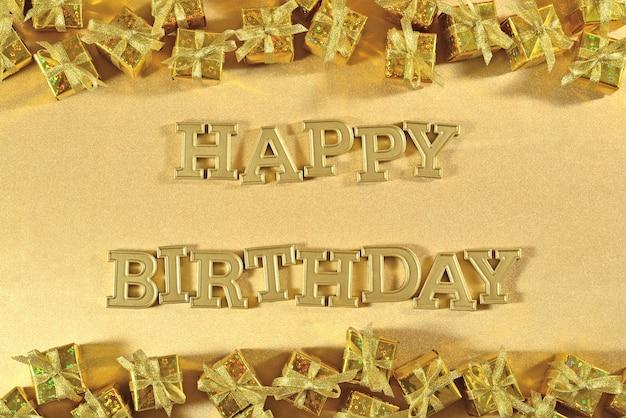 Texte d'or de joyeux anniversaire et cadeaux d'or sur un fond d'or