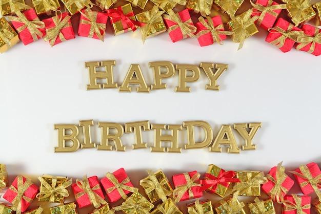 Texte d'or de joyeux anniversaire et cadeaux d'or et rouges sur un fond blanc