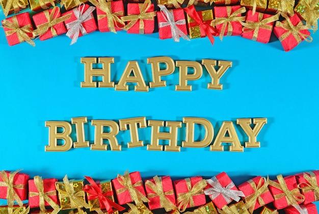 Texte d'or de joyeux anniversaire et cadeaux d'or et rouges sur un fond bleu