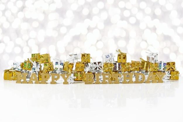 Texte d'or de joyeux anniversaire sur le fond des cadeaux d'or et d'argent sur un fond de bokeh