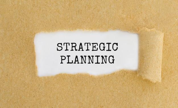Texte planification stratégique apparaissant derrière du papier brun déchiré