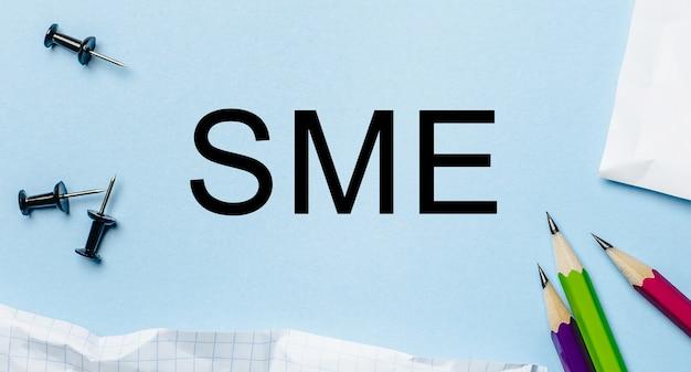 Texte pme sur un bloc-notes blanc avec des crayons sur un mur bleu