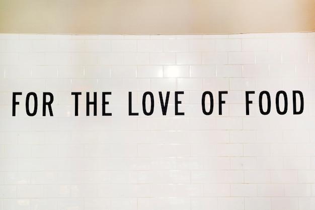 Texte pour l'amour de la nourriture sur un mur blanc