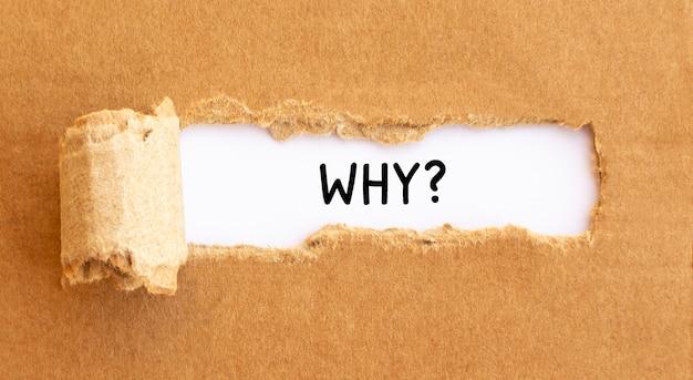 Texte pourquoi apparaître derrière du papier brun déchiré, concept