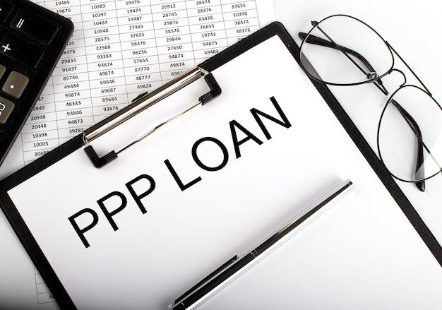 Texte de prêt ppp avec calculatrice, lunettes et stylo sur l'arrière-plan du graphique