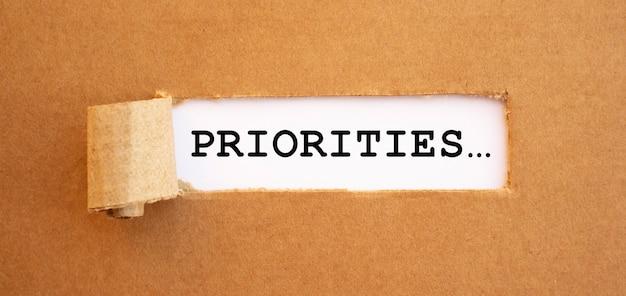 Texte priorités apparaissant derrière du papier brun déchiré.