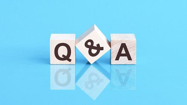 Le texte q et un écrit sur les cubes en lettres noires, les cubes sont situés sur une surface en verre bleu