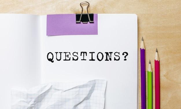 Texte de questions écrit sur un papier avec des crayons sur le bureau au bureau