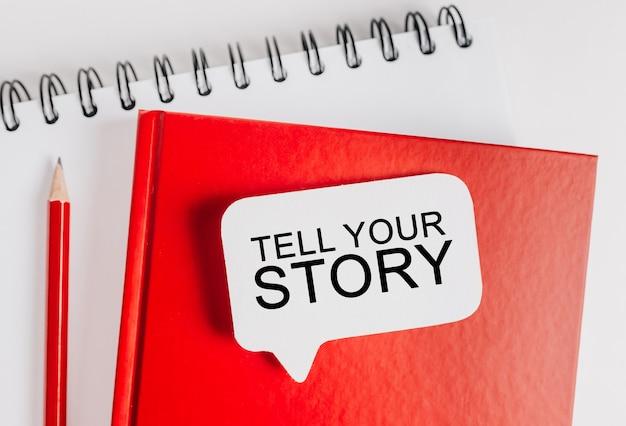 Texte racontez votre histoire sur un autocollant blanc sur le bloc-notes rouge avec espace de papeterie de bureau