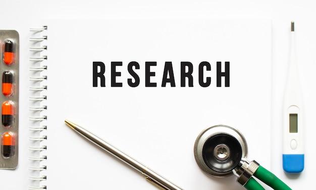 Texte de recherche écrit dans un cahier posé sur un bureau et un stéthoscope